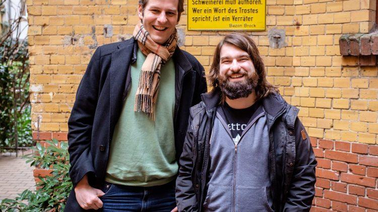 Jochen Markett und Andi Weiland (v. l.) suchen die Komik im Alltag. Auch beim Interviewtermin fällt den beiden sofort das Schild um die Ecke auf. Ein ideales Fotomotiv.