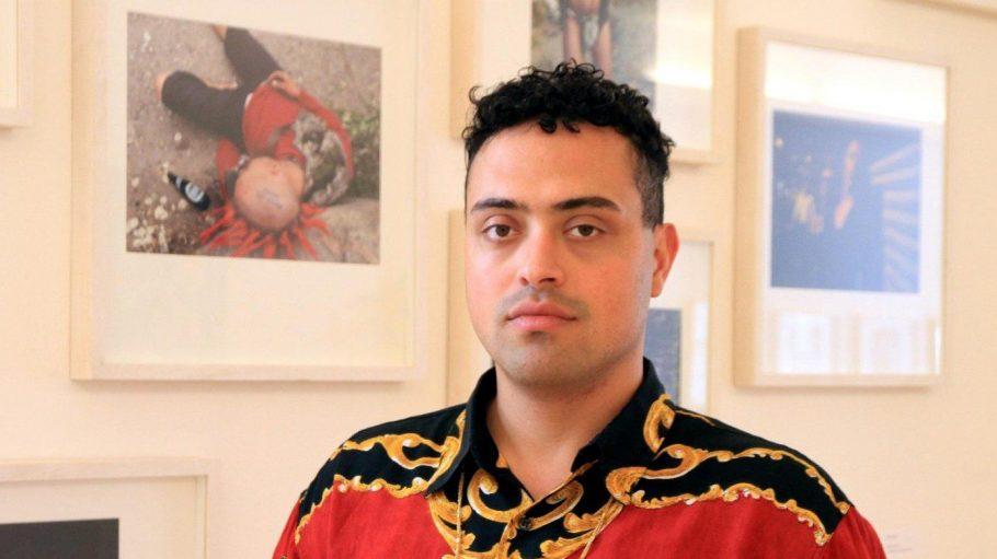 Regisseur Yony Leyser vor Bildern seiner Ausstellung.