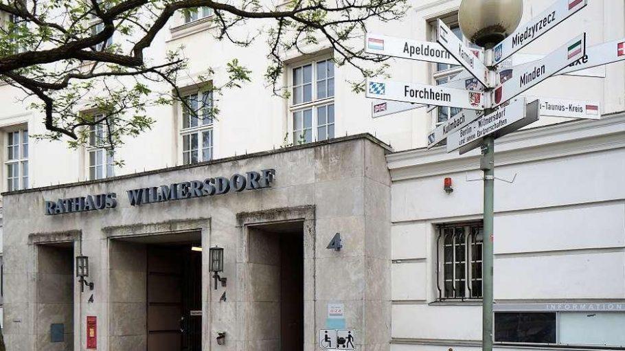 Relikt des Rathauses. Fünf Monate nach der Räumung am Fehrbelliner Platz soll der irreführende Schriftzug weichen. Die Schilder rechts weisen auf Partnergemeinden des Bezirks hin.
