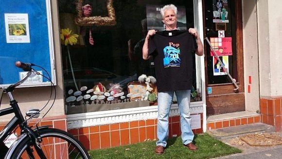 Vor dem Theater Zentral Rixdorf präsentiert Norbert Kleemann das T-Shirt zum Strohballenrollen Popráci.