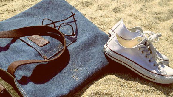 Eine Jeanstasche, eine Brille und Schuhe liegen im Sand. Ob wir im Standbad tegel nächstes Jahr noch alles abwerfen können?