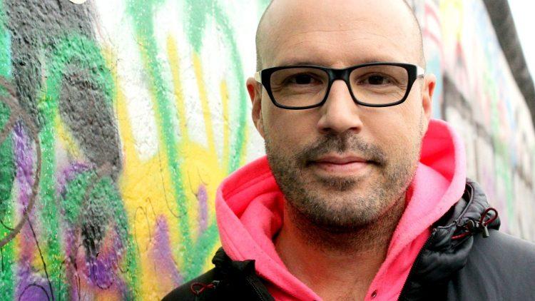 Christopher Deylen alias Schiller lehnt an einem Stück der Berliner Mauer. Er ist gern an der East Side Gallery oder im kleinen Park dahinter unterwegs.