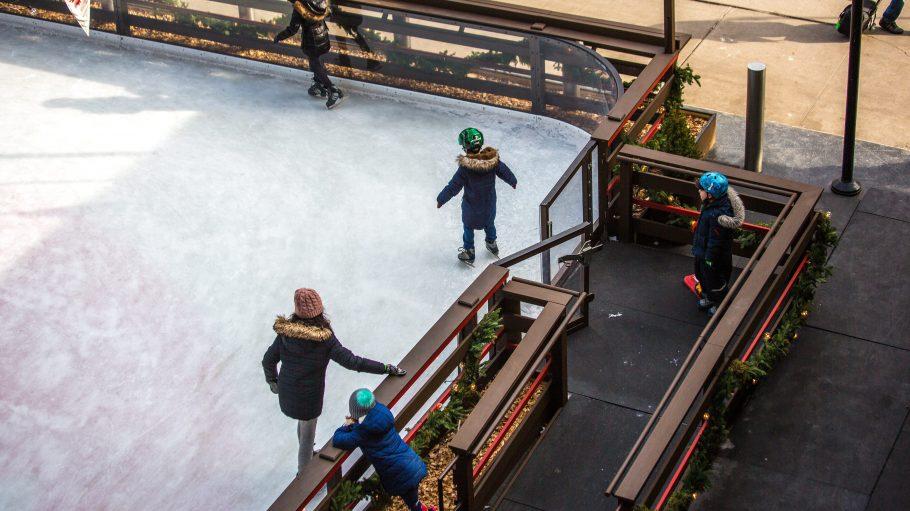 Kinder und Mutter von oeben, die auf einer Eislaufbahn stehen.