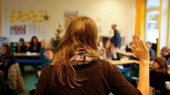 Die Tutorin einer Schulklasse gibt ihren Schützlingen per Handzeichen zu verstehen, dass sie ruhig sein sollen.