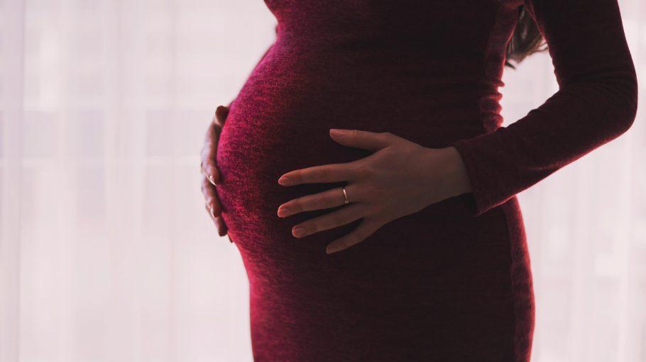 Schwangere Frau in rotem Kleid mit goldenem Ring am Finger.