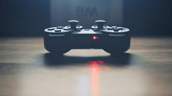 Schwarzer Joystick von Sony liegt auf dem Tisch mit rot blinkendem Lämpchen.