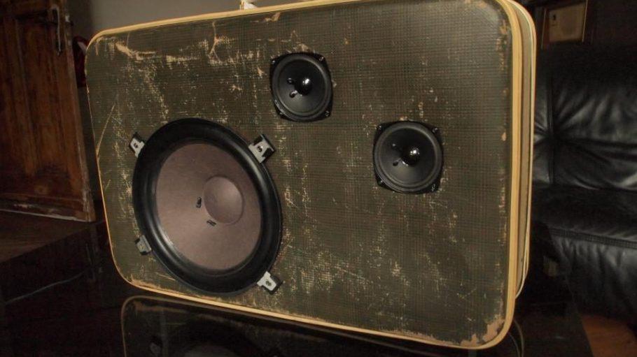 Ein alter Koffer mit sichtbaren Gebrauchsspuren dient als Hülle für eine mobile Musikanlage mit MP3-Anschluss.