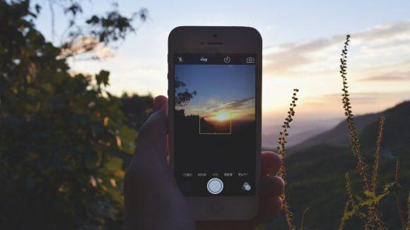 Jemand fotografiert mit seinem Smartphone des Sonnenuntergang. Das geht auch ohne W-Lan ...