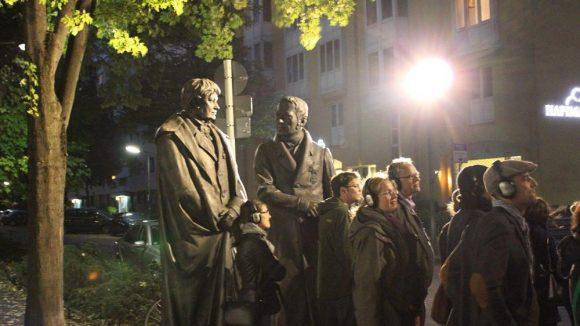 Mit Christian Peter Wilhelm Beuth und Wilhelm von Humboldt vor dem DIN-Gebäude. Gegenüber sprinten Mitglieder der Horde gerade um die Wette.