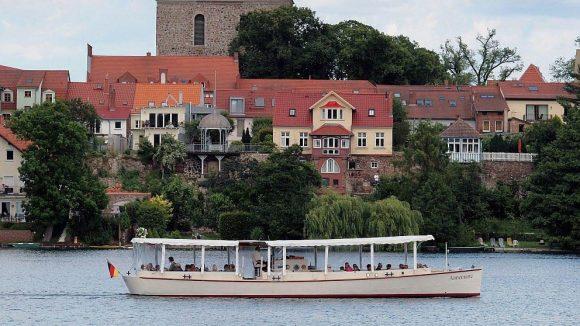 """Blick auf das Geburtstagskind Strausberg. Im Vordergrund sind der Straussee und das Ausflugsschiff """"Annemarie"""" zu sehen."""