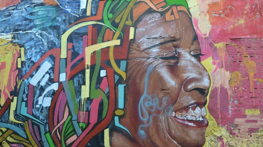 Eine von Herzen lachende Frau: Diese Streetart in Kolumbien reflektiert die Lebensfreude des glücklichsten Landes der Welt.
