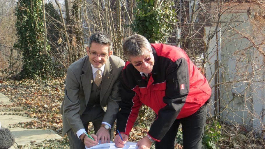 """Schworck und Marquardt (v.l.) unterschreiben den """"Regelkatalog"""" der Bahn AG, auf deren Gelände sich der umgebaute Bauwagen befindet."""