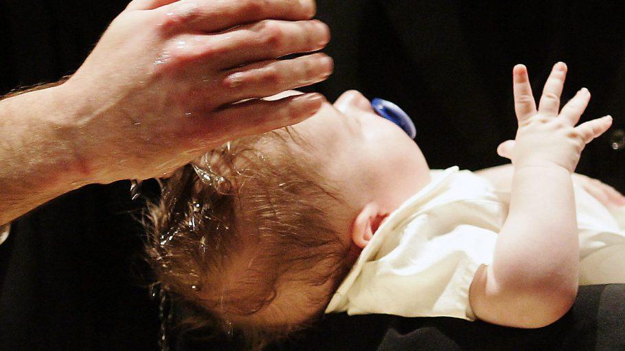 Ein Kind wird getauft.