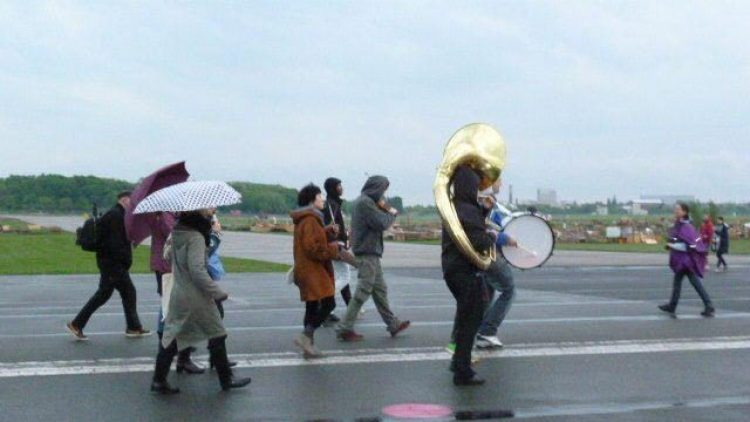 Trotz Regens macht sich die Gruppe auf den Weg: Mit Schirm, Charme und Tuba.