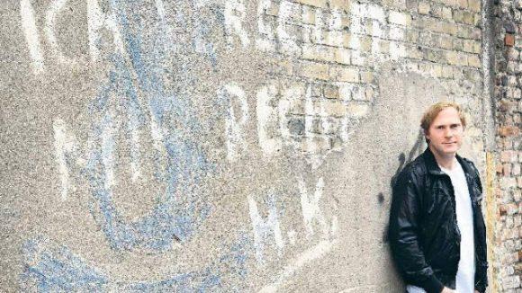 Sänger Thees Uhlmann vor graffitiverzierter Friedhofsmauer.