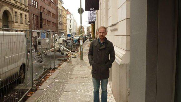 """""""Was Kunst anbelangt, sind wir am Puls der Zeit"""", sagt Wopp über seinen Kiez. Hier steht er vor den Kunstwerken."""