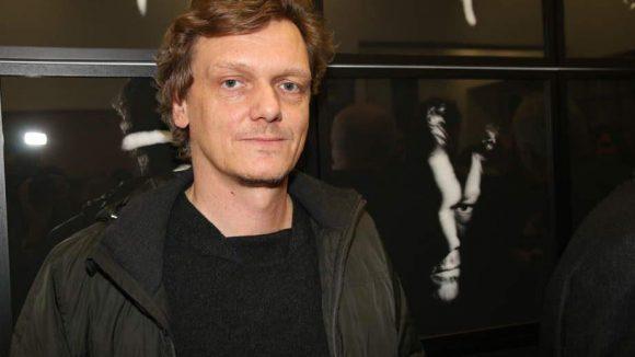 Der Chef der Berliner Festspiele Thomas Oberender steht direkt neben seinem Porträt.