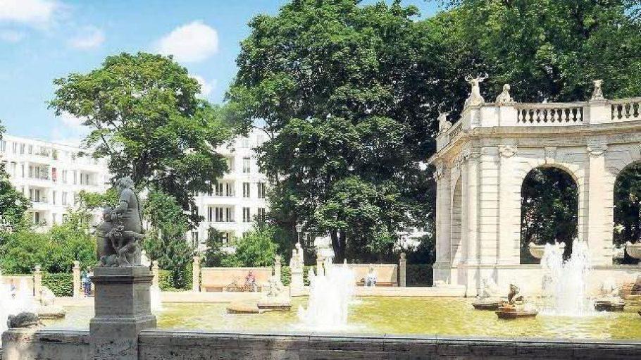 Schon seit 1913 plätschert der Märchenbrunnen im Volkspark Friedrichshain. Im Hintergrund: schicke Townhouses.