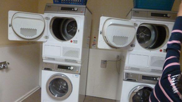 Tuana zeigt die zwei Waschmaschinen und Trockner des Waschcafés. Allein dürfen die Kinder diesen Raum nicht betreten.