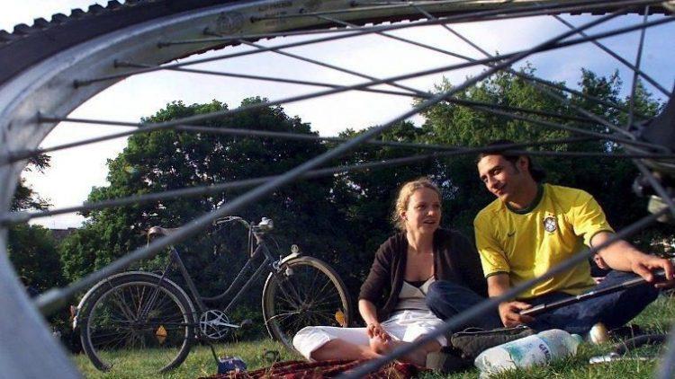 Ein Pärchen genießt die Sonnenstunden im Weinbergspark in Mitte.