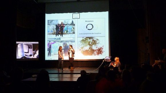"""Zwei Schülerinnen stellen die Arbeit während der Projektwoche vor. Auf dem Bildschirm links wird das Endprodukt, das Magazin """"Andersrum"""", eingeblendet."""