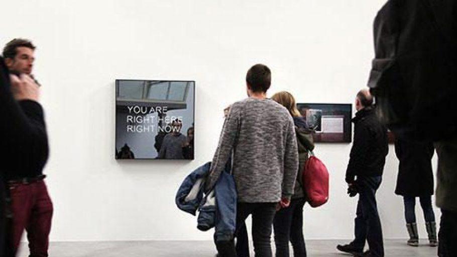 """Jeppe Hein lebt in Berlin und hat sein Werk """"You are right here right now"""" zur Ausstellung im """"Kindl"""" beigesteuert. Ein weißer Neonschriftzug befindet sich hinter einem Spionspiegel."""