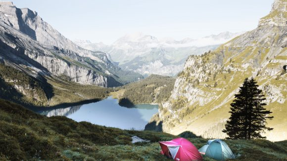 In einem Tal vor einem Bergsee stehen ein pinkes und ein blau-grünes Zelt auf der Wiese.
