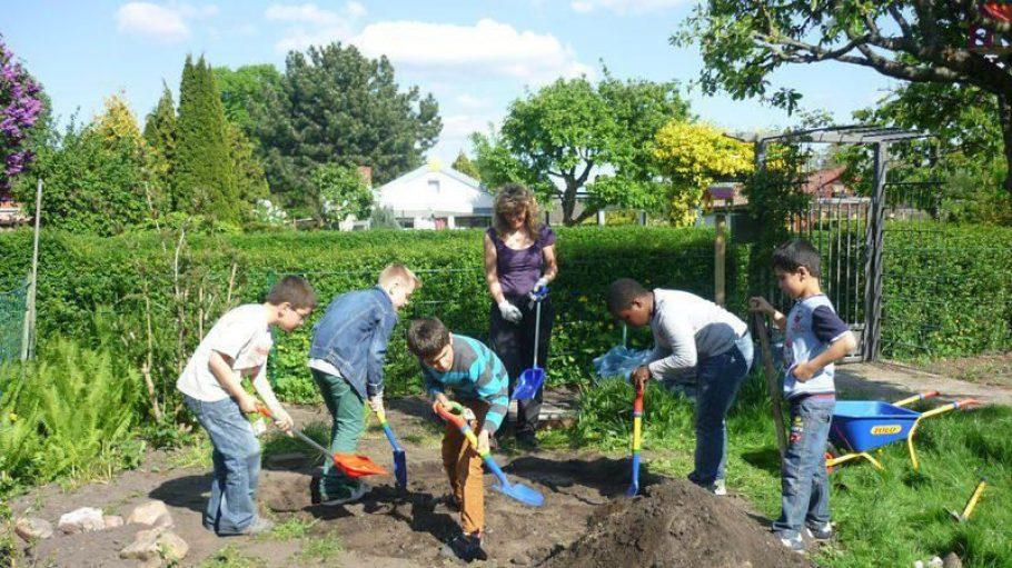 Die Kinder aus dem Malteser-Familienzentrum Manna nehmen zur Pflege des neuen Gartens die Schaufeln in die Hand.