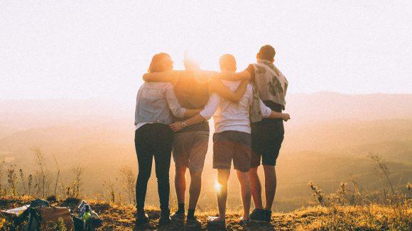 Vier junge Menschen stehen auf einem Hügel im Sonnenuntergang.