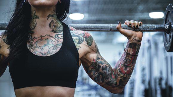 Frauentorse mit Tattoos stämmt Gewicht über den Schultern