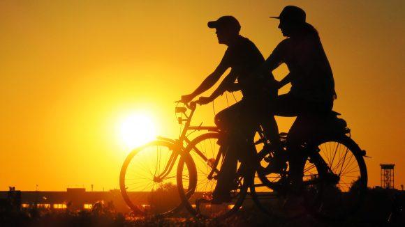 Die Silhouetten von zwei Radfahrern vor der untergehenden Sonne über dem Tempelhofer Feld