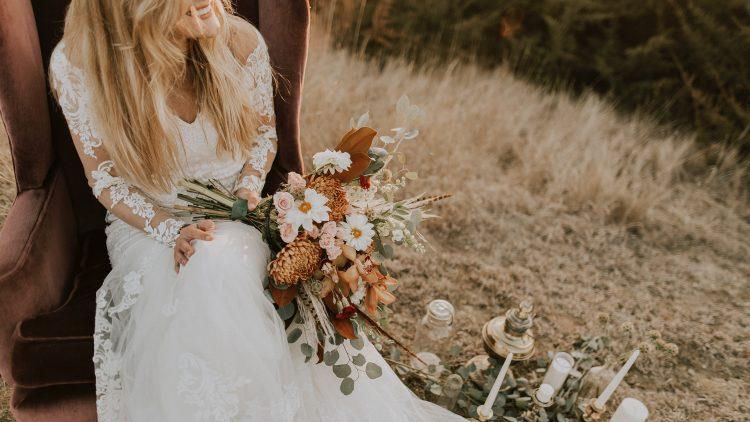 Braut in Vintage Hochzeitskleid mit langen Ärmeln aus Spitze auf einem Feld.