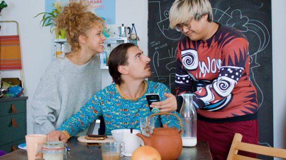 Am Frühstückstisch zeigt Joon (Joon Kim, r.) Lucia (Elli Tringou, l.) und Toni (Anton Weil, M.) die Bewertung der ersten Gäste. Die Mini-Serie Just Push Abuba startet am 16. März.