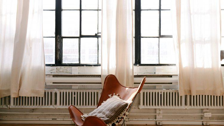 Ein brauner Ledersessel vor einer großen Fensterfront mit weißen Gardienen und einer Reihe von Heizkörpern und Heizungsrohren.