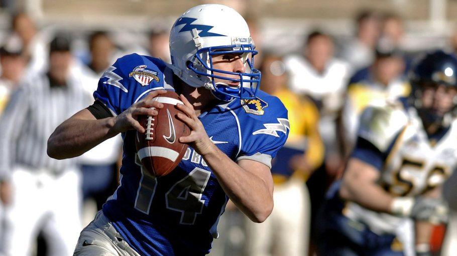 Ein Spieler in blauem Trikot rennt mit dem Football über das Feld.