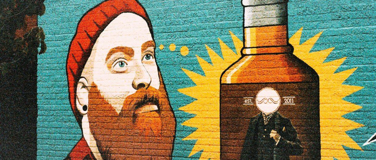 Gemaltes Wandbild eines bärtigen Mannes mit Bart und Mütze, der an ein Bier denkt.