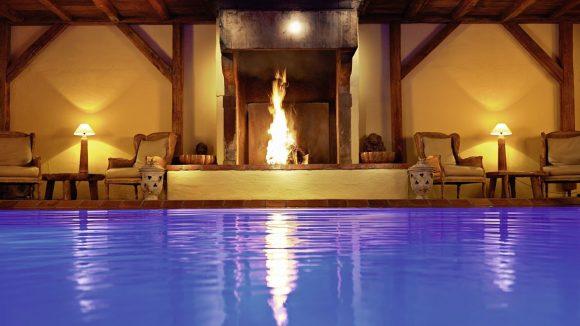 Großartige Kombi: offenes Feuer, warmer Pool und rustikales Gebälk.