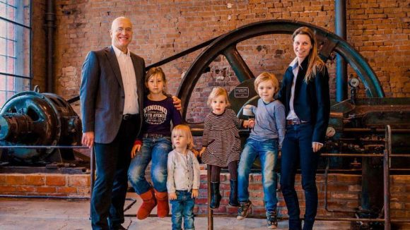 Inhaber Michael Stober mit seiner Frau Tanja Getto und ihren Kindern vor der historischen Dampfmaschine.