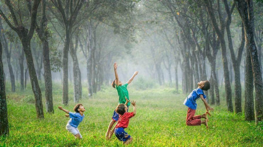 Vier Jungen spielen Ball auf einer Wiese im Wald