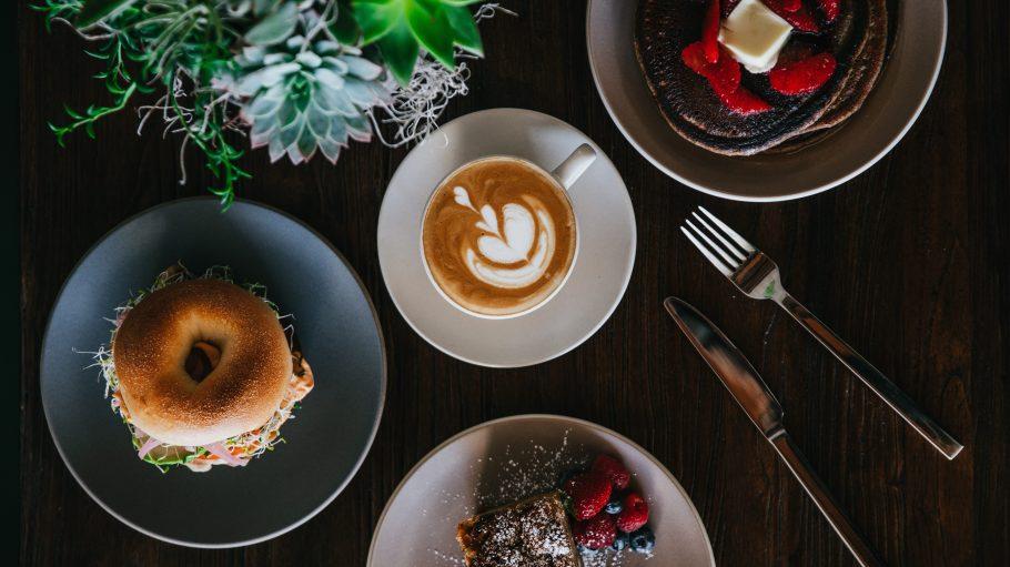 Bagel, Kaffee und Kuchen neben Sukkulente