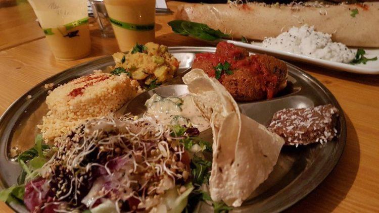 Bhima Thali im Goura Pakora mit verschiedenen Leckereien wie indische Falafel, Papadam und Salat. Dazu gibt's köstliche Mango Lassis.