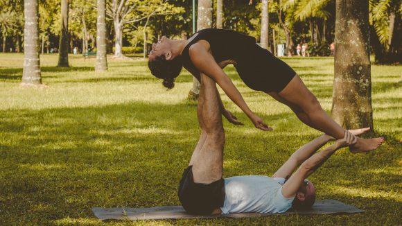 Zwei Menschen die in einem Park auf einer blauen Matte Yoga-Übungen zu zweit machen beim neuen Trend Acro-Yoga.