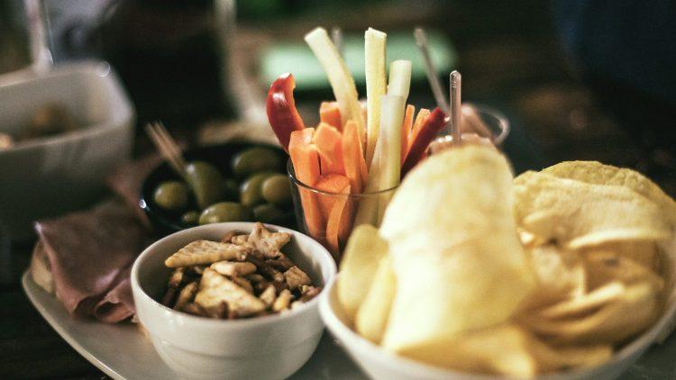 Ein Tisch voller Tapas zum Teilen mit Chips, Oliven und Gemüse.