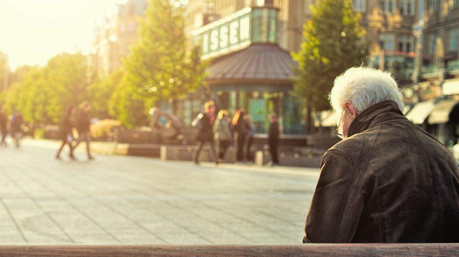 Älterer Mann sitzt alleine auf einer Parkbank in der Sonne Berlins.