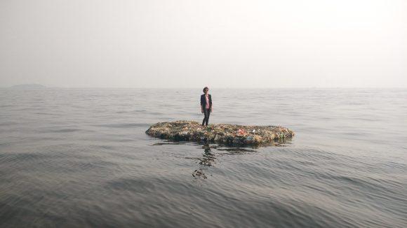 Eine Frau steht auf einer künstlichen Insel aus Plastik, die im Meer treibt.