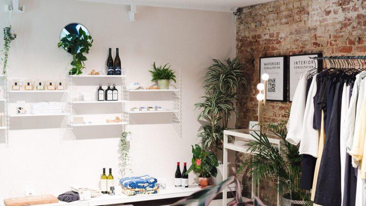 Ein Geschäft mit vielen weißen Regalen, Pflanzen, Weinflaschen, Decken und einer Kleiderstange.