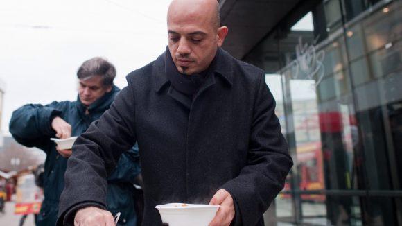Der aus Damaskus stammende Syrer Alex Assali gibt auf dem Alexanderplatz in Berlin Kartoffeleintopf an bedürftige Menschen aus.