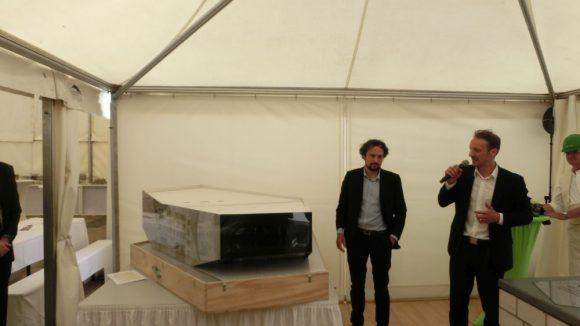 Voller Stolz enthüllen die Architekten Christoph Richter und Jan Musikowski bei der Grundsteinlegung am 10. Juni ein Modell vom Haus der Zukunft. Mit ihrem Konzept gewannen sie 2012 den Wettbewerb um die architektonische Ausgestaltung des Gebäudes.