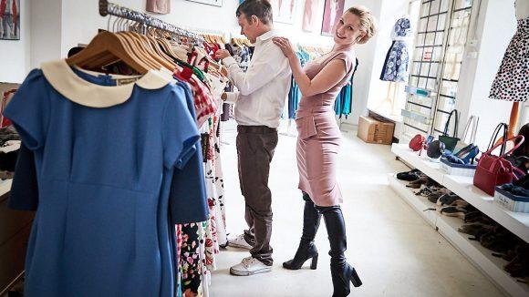 Marlene steht hinter dem Verkäufer Armin und schaut in die Kamera.