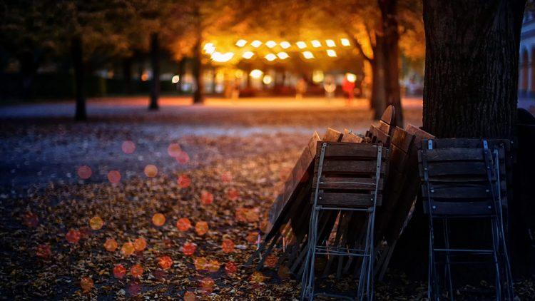 biergarten mit Schotterboden und zusammengeklappten Stühlen bei warmem Abendlicht